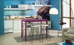 Niebieska kuchnia z tapetą. Aranżacja małej kuchni otwartej na salon