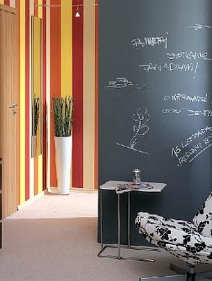 Ustawiona prostopadle do pasiastej ściana współtworząca salon została pomalowana czarną farbą, tzw. tablicówką, która kiedyś służyła do odnawiania tablic szkolnych